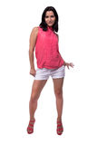 La mujer joven hermosa, atractiva en blusa y el cortocircuito pone en cortocircuito juguetónamente la sonrisa, presentando, mirad imagen de archivo libre de regalías