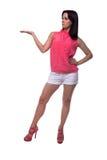 La mujer joven hermosa, atractiva en blusa y el cortocircuito pone en cortocircuito sostener un imaginario algo en la palma de su Fotografía de archivo libre de regalías