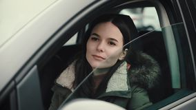 La mujer joven hermosa aumenta el vidrio de la puerta de su coche almacen de video