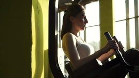 La mujer joven hermosa bombea para arriba la prensa en un cierre elegante del gimnasio para arriba MES lento metrajes
