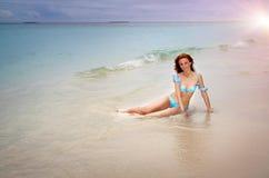 la mujer joven hermosa bronceada tiene un resto en ondas de la resaca Imagen de archivo