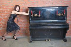 La mujer joven hermosa cambia de puesto el piano pesado imágenes de archivo libres de regalías