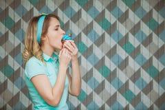 La mujer joven hermosa come el postre en un fondo azul Fotos de archivo libres de regalías