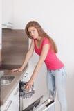 La mujer joven hermosa compuso los platos en el lavaplatos Imagen de archivo libre de regalías