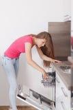 La mujer joven hermosa compuso los platos en el lavaplatos Fotografía de archivo
