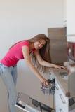 La mujer joven hermosa compuso los platos en el lavaplatos Foto de archivo