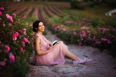 La mujer joven hermosa con el pelo oscuro que se sienta en las rosas coloca Aroma, cosméticos y publicidad del perfume fotografía de archivo