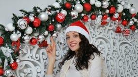 La mujer joven hermosa con el pelo rizado oscuro está tocando las bolas blancas y rojas de la Navidad en estudio adornado y la so almacen de metraje de vídeo