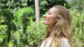 La mujer joven hermosa con el pelo rubio largo toma una respiración profunda