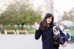 La mujer joven hermosa con el perro blanco adentro lleva el bolso Fotos de archivo