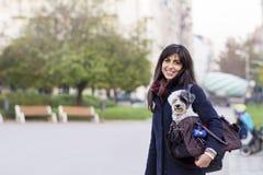 La mujer joven hermosa con el perro blanco adentro lleva el bolso Imagenes de archivo