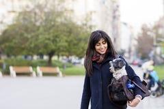 La mujer joven hermosa con el perro blanco adentro lleva el bolso Fotos de archivo libres de regalías