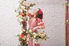 La mujer joven hermosa con la flor en pelo mantiene el bascket lleno de flores imagen de archivo