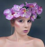 La mujer joven hermosa con la lila florece en pelo Fotos de archivo