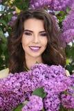 La mujer joven hermosa con la lila compone en jardín de la primavera Fotografía de archivo
