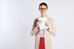 La mujer joven hermosa con los vidrios en un fondo de la luz sostiene un papel, profesor Imágenes de archivo libres de regalías