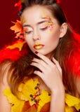 La mujer joven hermosa con otoño compone la presentación en estudio encima imagen de archivo libre de regalías