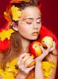 La mujer joven hermosa con otoño compone la presentación en estudio encima fotografía de archivo
