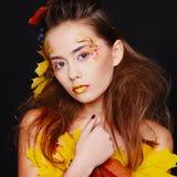 La mujer joven hermosa con otoño compone la presentación en estudio encima imagen de archivo