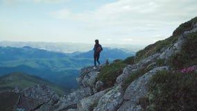 La mujer joven hermosa con una mochila se coloca solamente en la montaña alta, disfrutando de la visión Naturaleza hermosa, magní almacen de metraje de vídeo