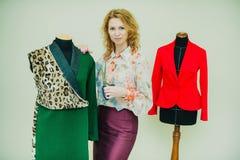 La mujer joven hermosa cose la capa del diseñador Capa y verde del estampado leopardo fotografía de archivo