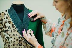 La mujer joven hermosa cose la capa del diseñador Capa y verde del estampado leopardo imagen de archivo