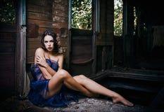 La mujer joven hermosa cubierta en paño se sienta en carro abandonado del tren Foto de archivo libre de regalías