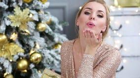 La mujer joven hermosa da un beso cerca del árbol de navidad metrajes