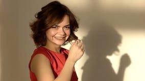 La mujer joven hermosa da vuelta alrededor, mirando la cámara y sonriendo en el cuarto Muchacha laughting Hay su sombra prendido almacen de video