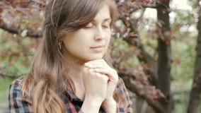 La mujer joven hermosa da vuelta a dios con sensaciones en rezo, la muchacha dobló sus brazos en su pecho y con miradas de la gra metrajes