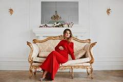 La mujer joven hermosa de la gestaci?n en vestido de noche rojo de moda se sienta en el sof? del vintage del oro en el interior d imágenes de archivo libres de regalías