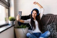 La mujer joven hermosa en casa disfruta de música que escucha Imagenes de archivo