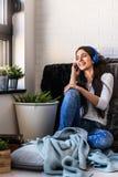 La mujer joven hermosa en casa disfruta de música que escucha Foto de archivo