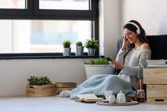 La mujer joven hermosa en casa disfruta de música que escucha Imagen de archivo libre de regalías
