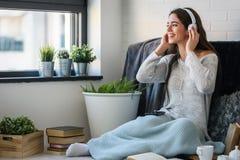 La mujer joven hermosa en casa disfruta de música que escucha Fotografía de archivo