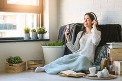 La mujer joven hermosa en casa disfruta de música que escucha Foto de archivo libre de regalías
