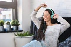 La mujer joven hermosa en casa disfruta de música que escucha Imágenes de archivo libres de regalías