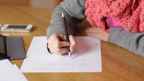 La mujer joven hermosa en la oficina escribe con la pluma almacen de metraje de vídeo