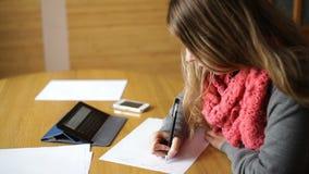 La mujer joven hermosa en la oficina escribe con la pluma almacen de video