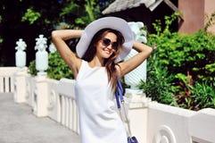 La mujer joven hermosa en la presentación elegante del sombrero y de las gafas de sol aventaja Foto de archivo libre de regalías