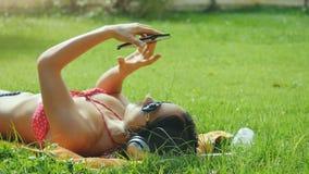 La mujer joven hermosa en las gafas de sol que mienten en la hierba, escuchando la música, utiliza el teléfono móvil y canción de Imágenes de archivo libres de regalías