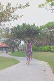 La mujer joven hermosa en pareo y el traje de baño que caminan en el becah parquean con el bolso en día de verano soleado Isla tr Fotografía de archivo