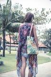 La mujer joven hermosa en pareo y el traje de baño que caminan en el becah parquean con el bolso en día de verano soleado Isla tr fotos de archivo