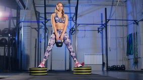 La mujer joven hermosa en ropa de deportes gris acaba de hacer ejercicio con el peso Ajuste de la cruz metrajes