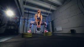 La mujer joven hermosa en ropa de deportes gris acaba de hacer ejercicio con el peso Ajuste de la cruz almacen de video