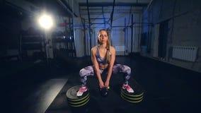 La mujer joven hermosa en ropa de deportes gris acaba de hacer ejercicio con el peso Cámara lenta almacen de video
