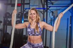 La mujer joven hermosa en ropa de deportes gris se aferra a una cuerda Ajuste de la cruz foto de archivo libre de regalías