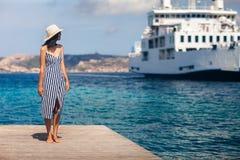 La mujer joven hermosa en sombrero se relaja en el embarcadero de madera en la playa de Cerdeña imagen de archivo