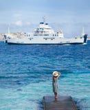La mujer joven hermosa en sombrero se relaja en el embarcadero de madera en la playa de Cerdeña foto de archivo libre de regalías