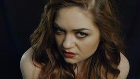 La mujer joven hermosa en un fondo negro muestra almacen de video